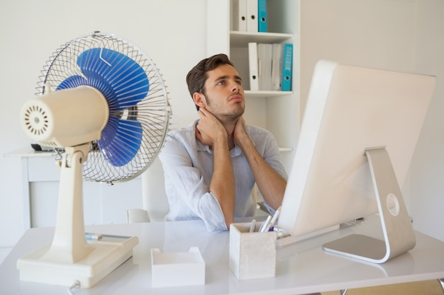 Przypadkowy biznesmena obsiadanie przy biurkiem z elektrycznym fan