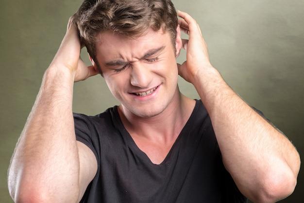 Przypadkowy caucasian młody człowiek cierpi na ból głowy