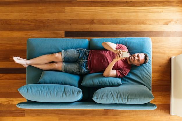 Przypadkowy facet na fotelu z smartphone