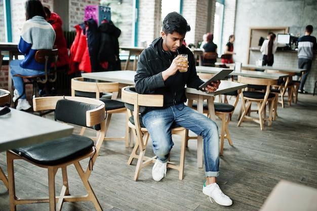 Przypadkowy i stylowy młody azjatykci mężczyzna z słuchawkami pije sok z szkła i trzyma pastylkę w kawiarni
