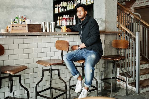 Przypadkowy i stylowy młody azjatykci mężczyzna z słuchawkami przy kawiarnią na barze pije sok ze szkła