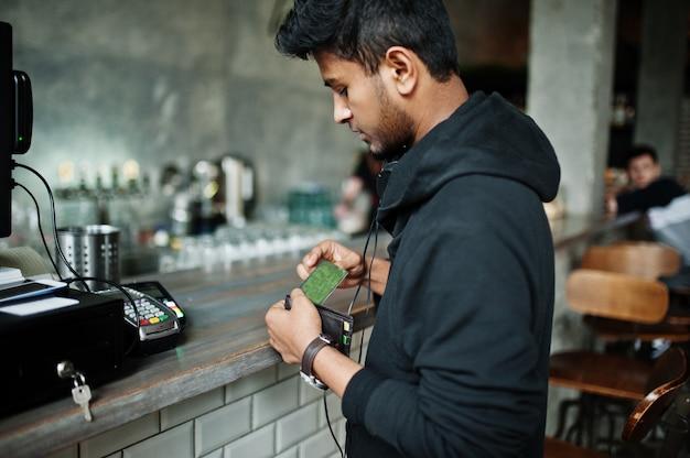 Przypadkowy i stylowy młody azjatykci mężczyzna z słuchawkami przy kawiarnią na barze płaci kartą kredytową