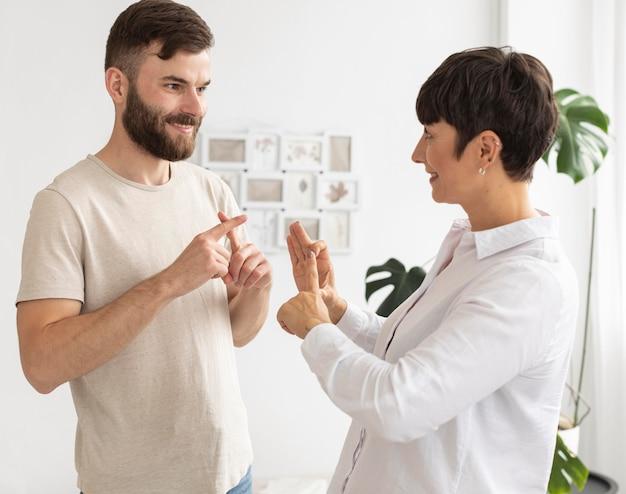 Przypadkowy mężczyzna i kobieta komunikują się za pomocą języka migowego