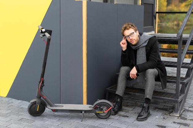 Przypadkowy mężczyzna pozuje obok skutera elektrycznego