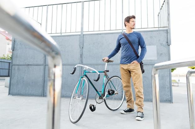 Przypadkowy mężczyzna pozuje z rowerem na zewnątrz
