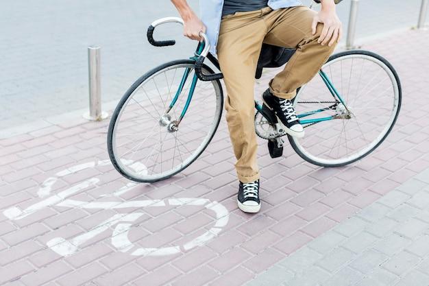 Przypadkowy mężczyzna siedzi na swoim rowerze