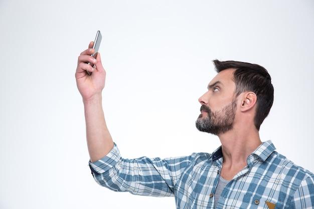 Przypadkowy mężczyzna szuka połączenia przez telefon lub robi zdjęcie selfie na smartfonie na białym tle na białej ścianie