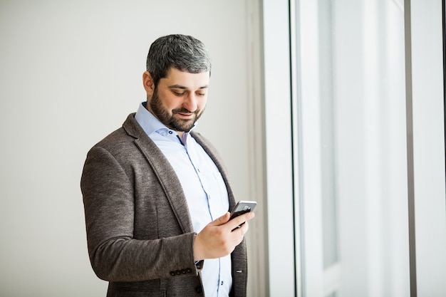 Przypadkowy miastowy fachowy biznesowego mężczyzna texting telefon szczęśliwy wśrodku biurowej sztandar panoramy