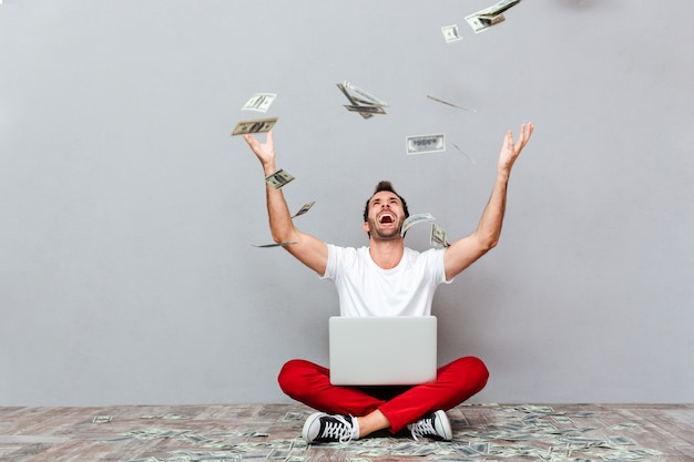 Przypadkowy młody człowiek siedzący na podłodze z deszczem pieniędzy na szarym tle