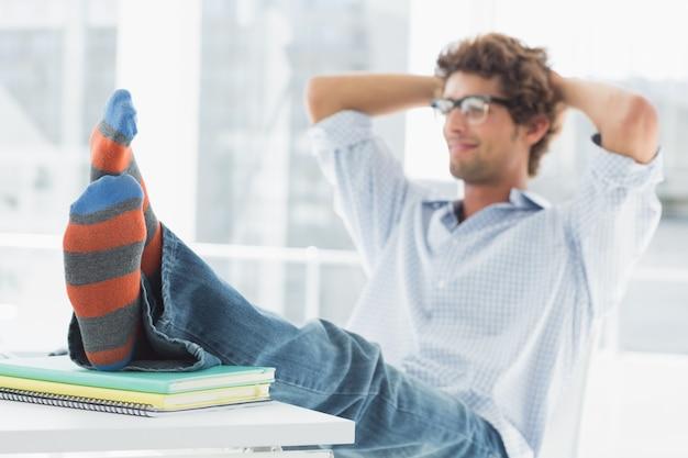 Przypadkowy młody człowiek z nogami na biurku w biurze