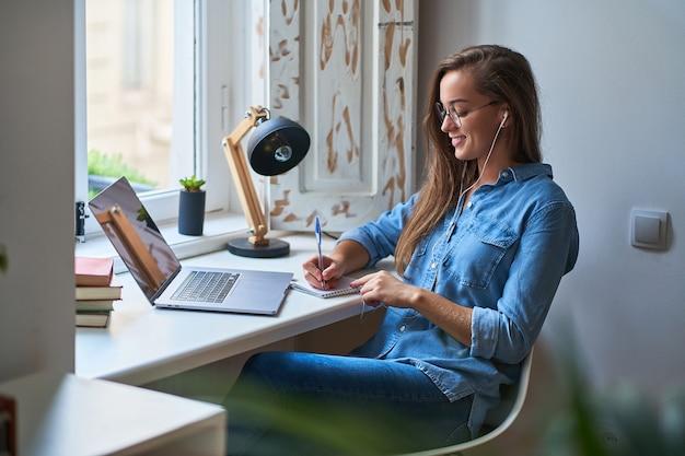 Przypadkowy młody uśmiechnięty inteligentny studentka w słuchawkach zadowolony z nauki języka obcego. kobieta robienie notatek w notatniku podczas oglądania kursów wideo seminarium internetowego. edukacja online