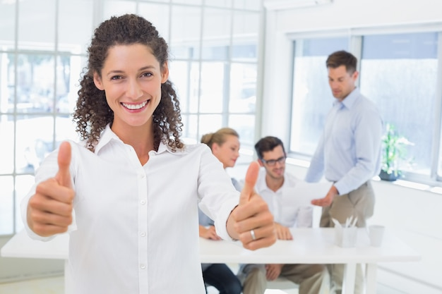 Przypadkowy szczęśliwy bizneswoman pokazuje kciuki do kamery