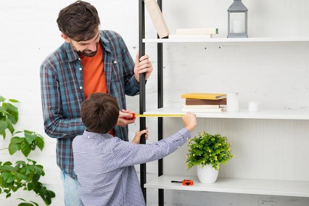 Przypadkowy ubierający ojciec i syn mierzy ja