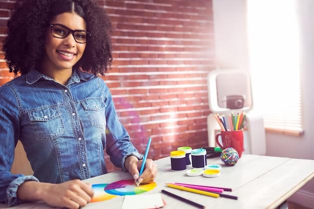 Przypadkowy żeński projektant ono uśmiecha się i rysuje
