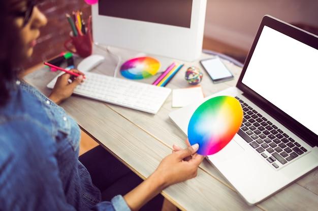 Przypadkowy żeński projektant patrzeje kolor mapę