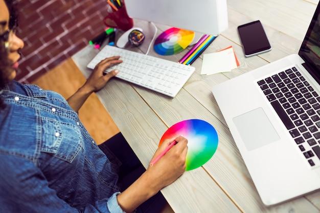 Przypadkowy żeński projektant pracuje z colour mapą