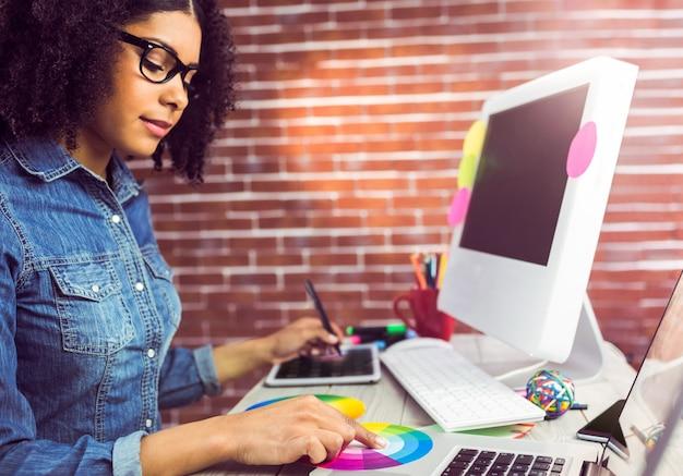 Przypadkowy żeński projektant pracuje z digitizer i colour mapą