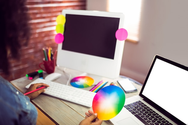 Przypadkowy żeński projektant pracuje z komputerem