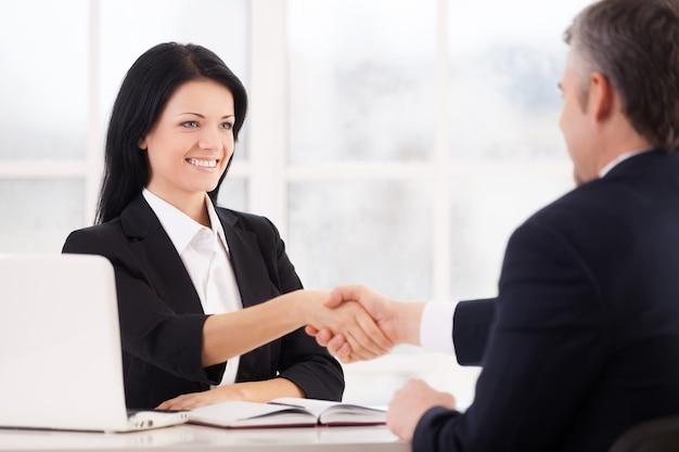 Przypieczętowanie umowy. dwóch wesołych ludzi biznesu ściskających dłonie i uśmiechających się siedząc twarzą w twarz przy stole
