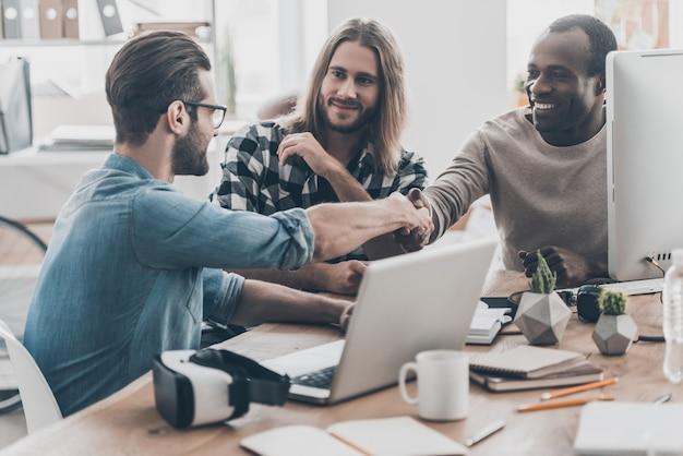 Przypieczętowanie umowy. trzech młodych ludzi odbywa spotkanie biznesowe w biurze, podczas gdy dwóch mężczyzn ściska dłonie i uśmiecha się