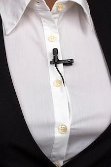 Przypinany mikrofon krawatowy jest przymocowany do odzieży damskiej z bliska. nagranie dźwięku głosu na mikrofonie pojemnościowym.