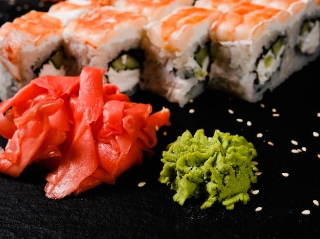 Przyprawa sushi marynowany imbir i wasabi. japońskie dania narodowe. roladki z krewetkami na ciemnym tle