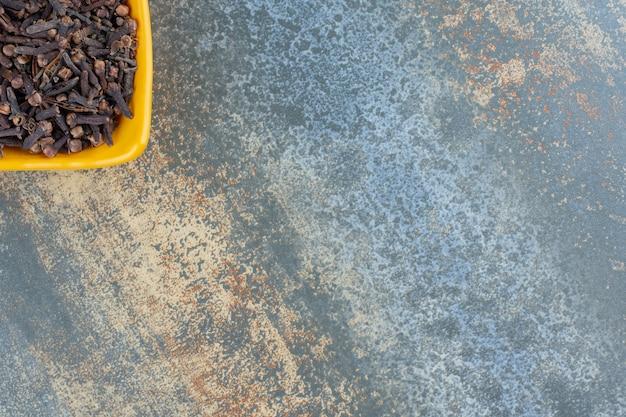 Przyprawa suszonych goździków w żółtej misce.