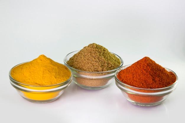 Przyprawa w proszku: chili, kurkuma i kolendra w misce na białym tle.