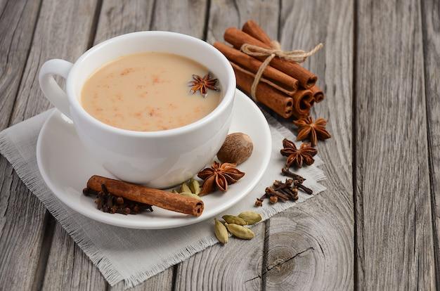 Przyprawiona herbata z mlekiem na rustykalnym drewnianym stole.
