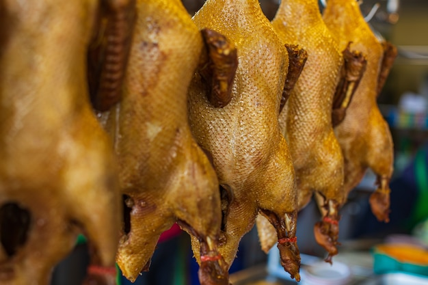 Przyprawiona kaczka lub duszona kaczka są zawieszone na nierdzewnych haczykach w tajlandzkim makaronie z kaczki