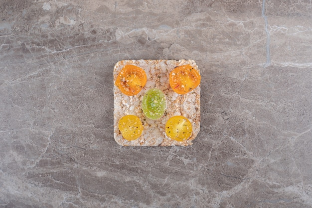 Przyprawione plastry pomidora z ciastem ryżowym pod spodem, na marmurowej powierzchni