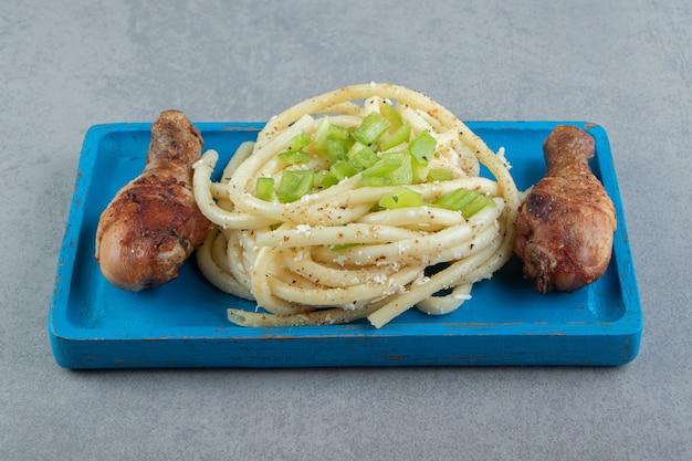 Przyprawione spaghetti i udka z kurczaka na niebieskim talerzu.