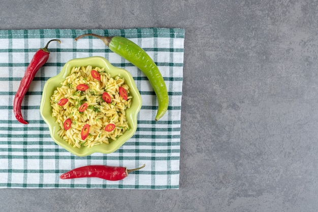 Przyprawiony ryż z pokrojoną papryką w zielonej misce. zdjęcie wysokiej jakości