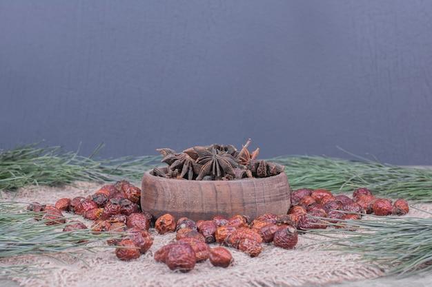 Przyprawy anyżowe w drewnianym kubku z biodrami