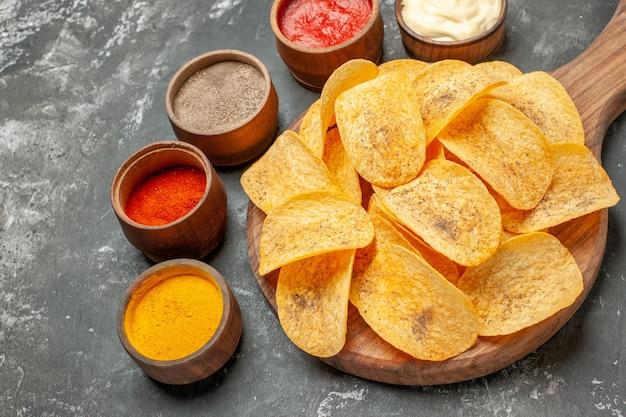 Przyprawy chipsy ziemniaczane i majonez z keczupem na drewnianej desce do krojenia na szarym stole