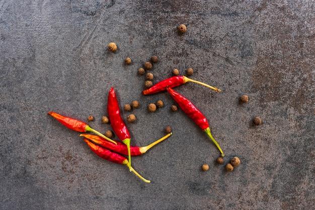 Przyprawy czarnego pieprzu i czerwonej ostrej papryki leżą na desce do krojenia z ciemnego kamienia