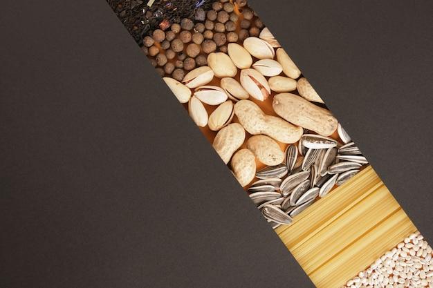 Przyprawy, herbata, płatki zbożowe, orzechy, nasiona i tekstura makaronu, czarny papier do tekstu kopia przestrzeń makieta, widok z góry koncepcja sklepu spożywczego