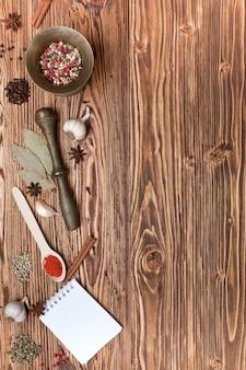 Przyprawy i notesy na drewnianym tle