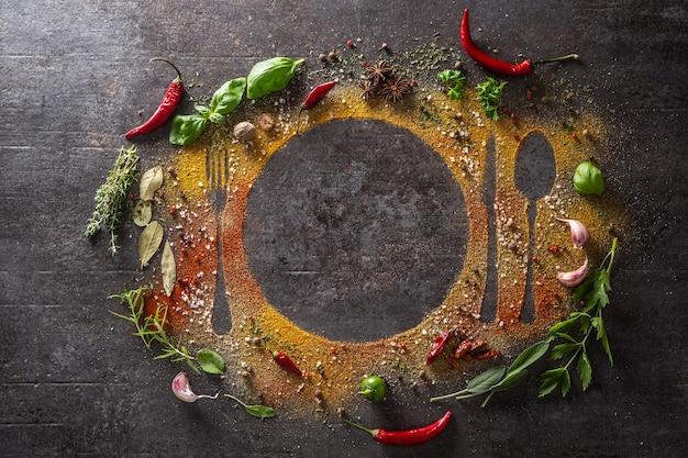 Przyprawy i zioła rozrzucone na stole tworzące sylwetkę sztućców i talerza - widok z góry.