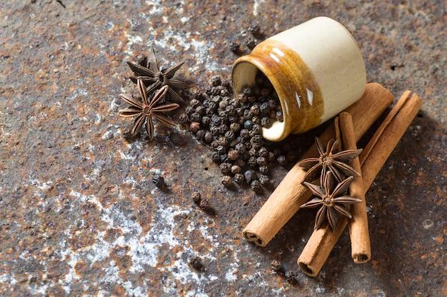 Przyprawy i zioła. składniki żywności i kuchni. laski cynamonu, gwiazdki anyżu i czarne ziarna pieprzu