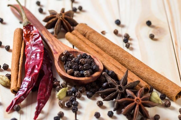 Przyprawy i zioła. żywność i składniki kuchni. laski cynamonu, gwiazdki anyżu, ziarenka czarnego pieprzu, chili, kardamon i goździki na drewnianej powierzchni