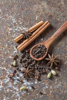 Przyprawy i zioła. żywność i składniki kuchni. laski cynamonu, gwiazdki anyżu, ziarenka czarnego pieprzu i kardamon na teksturowanej powierzchni.