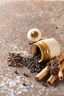 Przyprawy i zioła. żywność i składniki kuchni. laski cynamonu, gwiazdki anyżu, ziarenka czarnego pieprzu na teksturowanej powierzchni