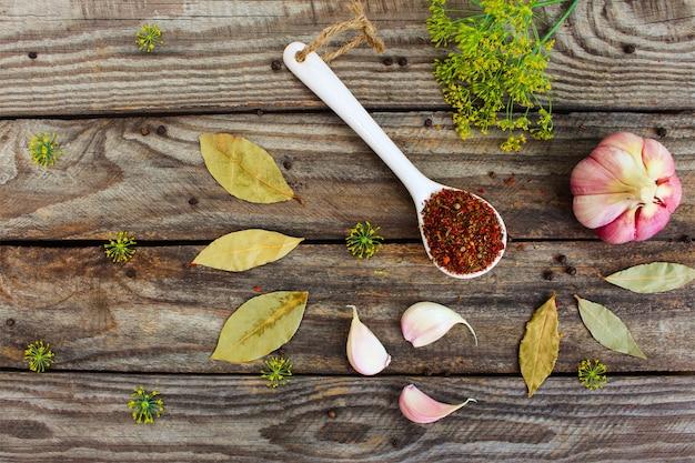 Przyprawy, liść laurowy, czarny pieprz, czosnek i koper na starym drewnianym