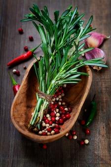 Przyprawy. papryczka chili, rozmaryn i czosnek. na drewnianym stole