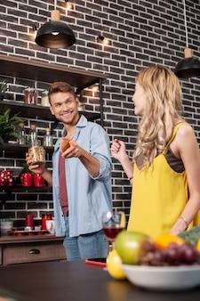 Przyprawy. pomocny, przystojny, rozpromieniony mąż bierze trochę przypraw podczas gotowania obiadu ze swoją kobietą