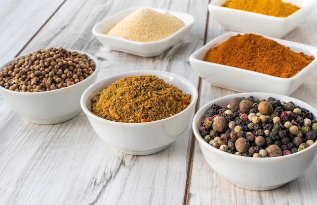 Przyprawy w białych miseczkach na drewnianym stole. żywność i składniki kuchni do gotowania.