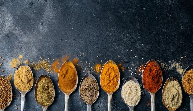 Przyprawy w tle łyżki. odmiany przypraw (kurkuma, pieprz, chili, kolendra, cynamon) i papryki do gotowania. koncepcja kulinarnej żywności.