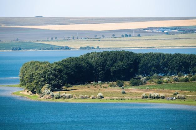 Przyroda mołdawii, łąka z wiejską drogą, bujnymi drzewami i odpoczywającymi ludźmi, jezioro, pola i widoczne w oddali rzadkie budowle