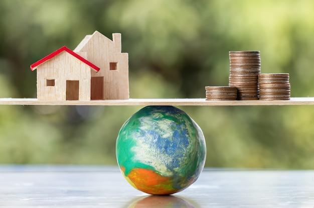 Przyroda środowisko globalne / ochrona / ratowanie świata koncepcja: świat musi dźwigać duże ciężary ludzi, którzy chcą wydać pieniądze na budowę domu / nieruchomości. stał się częścią niszczenia natury